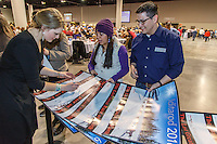 Lisbet Norris signs a gaggle of Iditarod posters for race fans at the 2016 Iditarod musher position drawing banquet at the Dena'ina convention center in Anchorage, Alaska on Thursday March 3, 2016  <br /> <br /> © Jeff Schultz/SchultzPhoto.com ALL RIGHTS RESERVED<br /> DO NOT REPRODUCE WITHOUT PERMISSION
