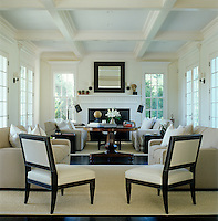There are no curtains at the windows of this wonderfully symmetrical black, white and cream East Hampton living room and it is flooded with natural light