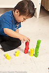 Three year old boy building towers of colored wooden cubes sorting them by color at home