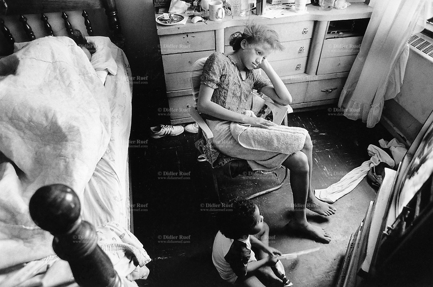 """USA. New York City. Spanish Harlem. The mother Nina (L) is sleeping in the bed, while both her children Sala and Papo are watching a program on television. The Puerto Rican family lives below the poverty line and receives public assistance (AFDC, Home Relief, Supplemental Security Income and Medicaid). The family resides in units managed by the New York City Housing Authority (NYCHA) which provides housing for low income residents. NYCHA administers rental apartments in facilities, popularly known as """"projects"""". Spanish Harlem, also known as El Barrio and East Harlem, is a low income neighborhood in Harlem area. Spanish Harlem is one of the largest predominantly Latino communities in New York City. 10.06.88 © 1986 Didier Ruef ."""