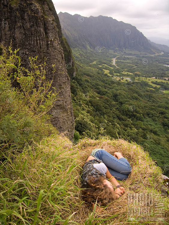 A young local woman rests near the Pali Lookout, with Kane'ohe and the Ko'olau Range in the distance, O'ahu.