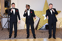 Pictured: The Rat Pack act performs. Wednesday 28 November 2018<br /> Re: National Lottery millionaires from south Wales and the south west of England have hosted a glitzy Rat Pack-inspired Christmas party for an older people's music group at The Bear Hotel in Cowbridge, Wales, UK.