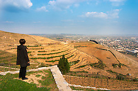 The graphic curved terraces in the Chapelle vineyard. A woman in black standing looking out over the vineyard. The Hermitage vineyards on the hill behind the city Tain-l'Hermitage, on the steep sloping hill, stone terraced. Sometimes spelled Ermitage. Vineyards; Chapelle in front, Chante Alouette and Le Meal in the background Tain l'Hermitage, Drome, Drôme, France, Europe