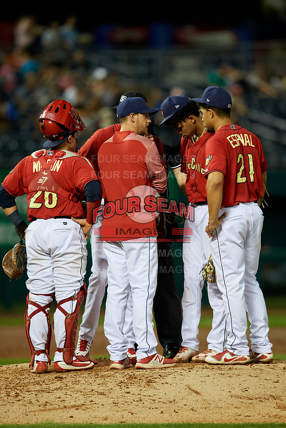 State College Spikes pitching coach Adrian Martin (15) in a mound visit with catcher Alexis Wilson (26), starting pitcher Diego Cordero (11), shortstop Delvin Perez (23) and third baseman Stanley Espinal (21) as home plate umpire Benjamin Engstrand listens in during a game against the West Virginia Black Bears on August 30, 2018 at Medlar Field at Lubrano Park in State College, Pennsylvania.  West Virginia defeated State College 5-3.  (Mike Janes/Four Seam Images)