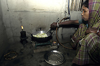 jbo11519 renewables green Energy environment climate biogas biomass energy from buffalo and cow dung for biogas plant in village India southasia gobergas woman cooks with biogas preparing food nutrition stove fire .Umwelt Klimaschutz erneuerbare alternative Energie aus Kuhdung für Biogasanlage zum Kochen und Heizen in Dorf Indien Südasien Frau kochen mit Biogas Ernährung Herd feuer.copyright Joerg Boethling / agenda