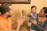 Young couple in 20s with 16 month old toddler son singing song with hand gestures