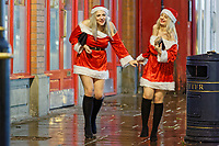 Pictured: Two young women in Santa outfits walk down Wind Street, Swansea, south Wales, UK. Friday 21 December 2018<br /> Re: Black Eye Friday, also known as Mad Friday or Black Friday which is the last Friday before Christmas Day.