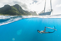 A woman free dives off an anchored sailboat on the Na Pali Coast of Kaua'i.