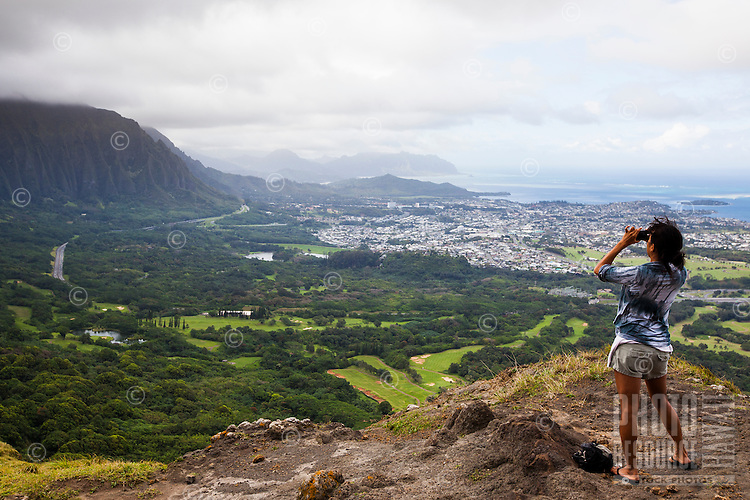 A woman looking through binoculars from a cliff overlooking beautiful Kaneohe Bay, Oahu.
