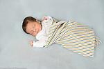 12 day old newborn baby boy sleeping swaddled on back