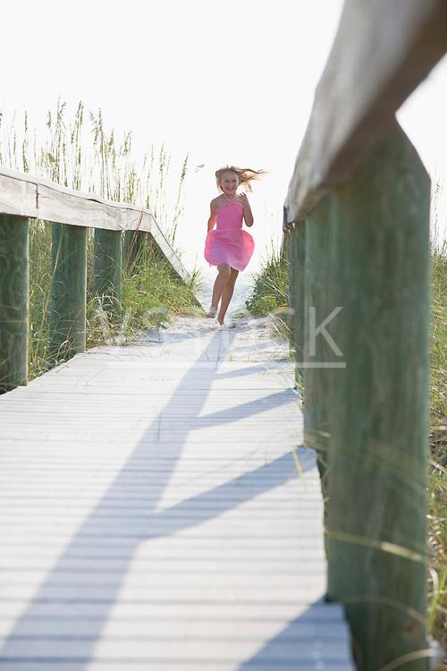 USA, Florida, St. Pete Beach, Girl (8-9) running on boardwalk