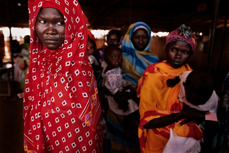 Women wait in line for food for their undernourished children.  They live in a refugee ring outside the city of Khartoum.  This refugee ring is the largest in the world--4 million people seek refuge here...Story Summary:.Sudan, the largest country in Africa, hosts a civil war between the Islamic North and the African South that has the highest casualty rate of any war since World War II...Two and a half million people have been killed in this insidious conflict.  It drags on because Southerners have no voice, and the Northerners have engineered ÒThe Perfect WarÓ where none of their people are killed...The North forces people out of the South by bombing them, burning their crops, and harassing them with gunships. They abduct their children and draft them to fight with the Northern armyÑforcing southerners to fight their own brothers...This story is particularly interesting now because there is a small window for peace in a civil war that has been dragging on since the end of colonial rule.  The war has always been about tribal issues and ideologyÉ but more than that, it is about resources.  This clash over resources may bring peace.  The North controls the pipeline and the only port, and the South controls the land...The story of Sudan has always been the continual transference of wealth from the resources of the south to the elite few who live in the deserts of the north.  And the sucking sound in the middle of the country is from the corrupt government in northern Khartoum..