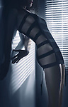 Sexy edgy fashion photo of a beautiful woman in stripy black underwear standing with her body arched in a seductive curve in dim window light Image © MaximImages, License at https://www.maximimages.com
