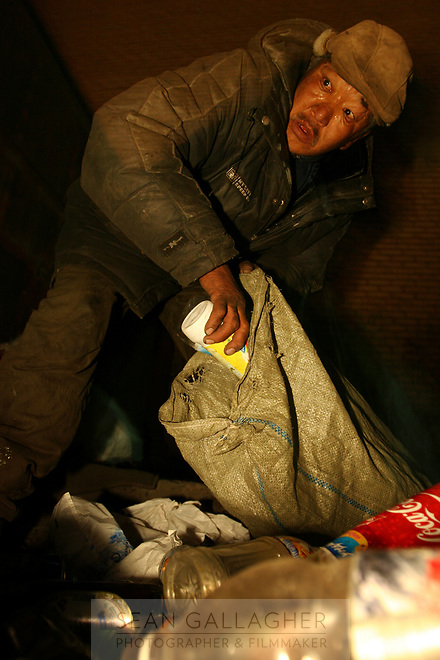 MONGOLIA. Ulaan Baatar. Battur,55,  searches for bottles through piles of refuse, mainly found outside apartment buildings throughout the city.As the global financial crisis grips Asia, Mongolia is feeling the implications first hand as the country suffers from rising inflation pushing the price of food and fuel ever upwards. For the country's homeless, who live in sewers and abandoned garages in the capital and already face extreme discrimination and are denied access to basic health and social care, their lives are hanging in the balance. 2008
