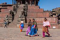 Bhaktapur, Nepal.  Women Crossing Taumadhi Tole Square.  Rajput Wrestler-guardians Jayamel and Phattu  Guard Stairs leading to Nyatapola Temple.