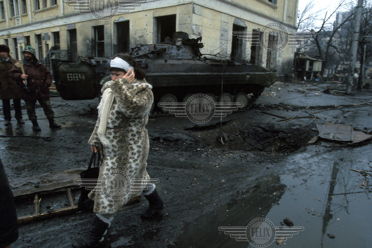 A woman in a fur coat walks past the wreckage of a Russian APC in Grozny city centre..In December 1994 Russian troops entered Chechnya in an attempt to quash the countryÕs independence movement.  Early promises of a quick victory were soon silenced as the Chechens put up fierce resistance to the Russian assault and the death toll mounted.  Up to 100,000 people Ð many of them civilians Ð are estimated to have been killed in the 20 month war that followed.