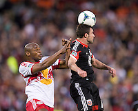 Chris Pontius (13) of D.C. United goes up for a header in front of Jamison Olave (4) of New York Red Bulls during the game at RFK Stadium in Washington, DC.  New York Red Bulls defeated D.C. United, 2-0.