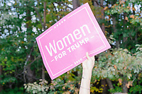 """A woman holds a sign reading """"Women for Trump"""" as Donald Trump, Jr., son of president Donald Trump and a rising Republican political star, speaks at an outdoor campaign rally at The Lobster Trap in North Conway, New Hampshire, on Thu., Sept. 24, 2020. Johnson said that the president had signed her """"Hot chicks for Trump"""" button and her hat at earlier rallies."""