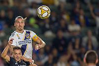 CARSON, CA - SEPTEMBER 15: Zlatan Ibrahimovic #9 of the Los Angeles Galaxy goes up high over Luis Martins #36 of Sporting Kansas City during a game between Sporting Kansas City and Los Angeles Galaxy at Dignity Health Sports Park on September 15, 2019 in Carson, California.