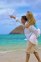 Couple playing on white sand beach on their honeymoon in Hawaii