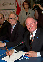 June 6 , 2002, Montreal, Quebec, Canada<br /> <br /> Bernard Landry, Quebec Premier (R), <br /> Gerald Tremblay, Montreal (new) Mayor (M)<br /> Frank Zampino, Montreal City Executive Commitee (L)<br /> smiles for photographers as they sign a partnership agreement between the Quebec Gouvernment and the <br /> new City of Montreal (after all cities on the Montreal islanf merged with Montreal City), <br /> at the closing of the Montreal Summit (Le Sommet de Montr»al), June 6, 2002