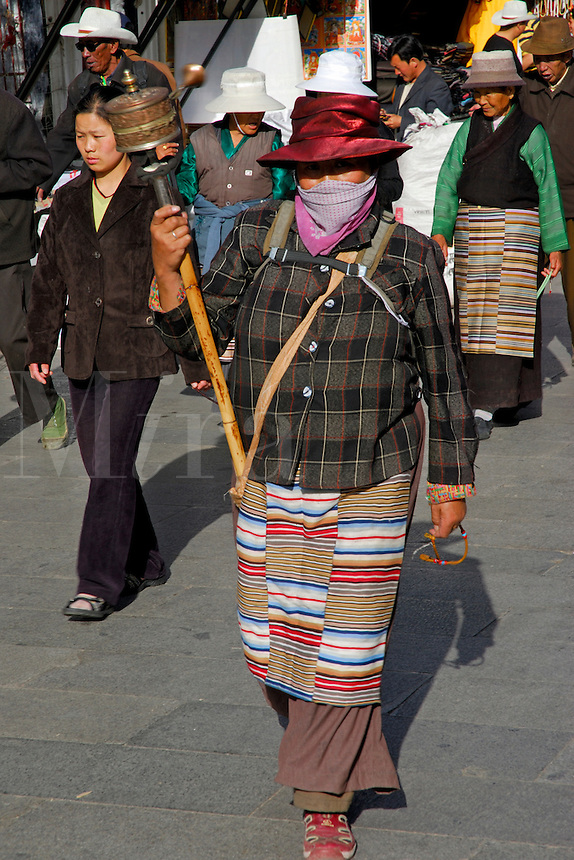 Tibetan woman wearing traditional striped apron, with prayer wheel and mala beads, walking the Barkhor pilgrim circuit around the Jokhang Temple, Lhasa, Tibet.