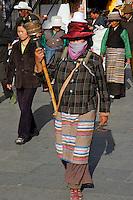 Tibetan woman wearing traditional striped apron, with prayer wheel and mala beads, walking the Barkhor pilgrim circuit around the Jokhang Temple, Lhasa, Tibet.