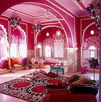 The flamboyantly colourful living room with its custom-made glass chandeliers and vivid cushions and textiles
