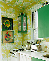 Clever continuation of the wallpaper across the ceiling demarcates the kitchen from the hallway. The emerald green accents in the toile de jouy paper are echoed in the picture frames and cabinets. The old gas cooker and retro-style Dualit toaster and food processor bring a decidedly retro feel.