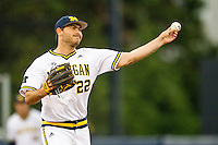 Michigan Wolverines pitcher William Tribucher (22) makes a pickoff throw to first base against the Oakland Golden Grizzlies on May 17, 2016 at Ray Fisher Stadium in Ann Arbor, Michigan. Oakland defeated Michigan 6-5 in 10 innings. (Andrew Woolley/Four Seam Images)