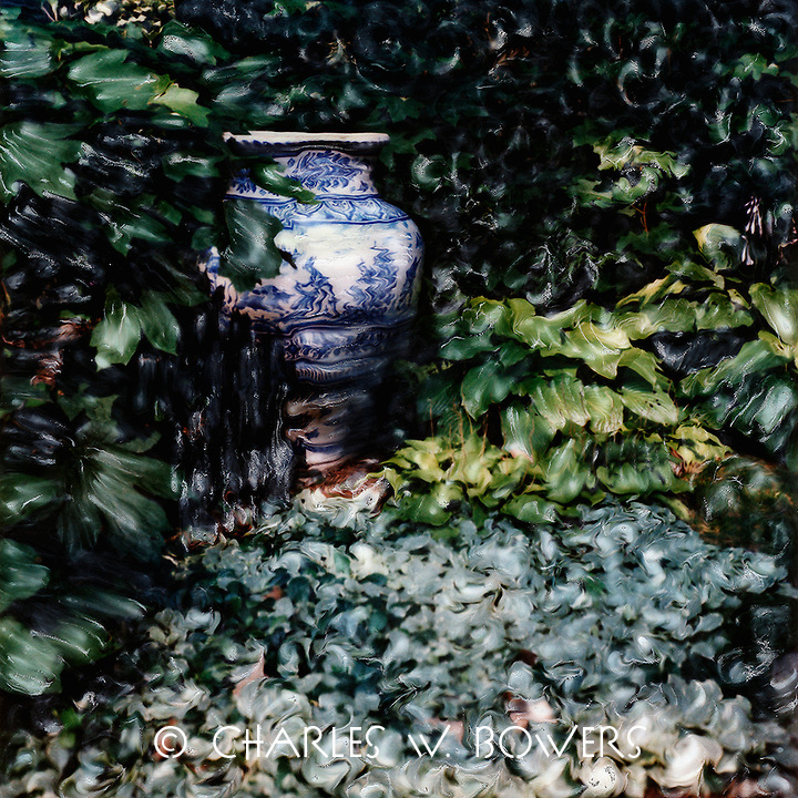 A Blue Urn in the garden. Urn with Oriental influence sits in a comfortable location surrounded by green and lush foliage. A picturesque and fitting home.<br />