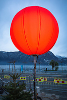 Switzerland. Canton Ticino. Lugano. A red heavy duty lighting balloon is used for evening lightings during the traditional Christmas market, which takes place on Piazza Riforma during the month of december. The complete kit for operation includes a luminous ballon, the power socket and a DC high-current switch. View on Lake Lugano and the waterfront. 9.12.2020 © 2020 Didier Ruef