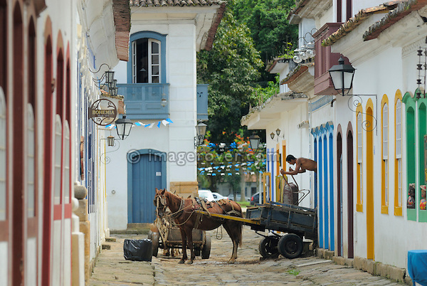 Local brazilian builder using a horse cart and wheelbarrow to renovating one of the charming houses in Paraty's historic centre; Paraty, Espirito Santo, Brazil. --- Info: The beautiful colonial town of Paraty has been a UNESCO World Heritage Site since 1958. --- No signed releases available.