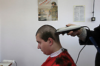 Conscript Kamil Wozniak has his head shaved, under a poster advertising the new, voluntary Polish army. This year's class of drafted recruits is the final one after 90 years of compulsory military service, as Poland's army turns professional in 2009.