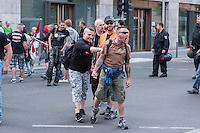 """Neonazis und Hooligans demonstrieren gegen Angela Merkel.<br /> Unter dem Motto """"Merkel muss weg"""" zogen ca. 1.200 am Samstag den 30. Juli 2016 mit einer Demonstration durch Berlin. Der Aufmarsch war vom einschlaegig bekannten Neonazi-Hooligan Enrico Stubbe angemeldet worden.<br /> Die Polizei hatte die Aufmarschroute der Rechten weitraeumig abgesperrt.<br /> Die Rechten forderten in Sprechchoeren immer wieder """"Nationalen Sozialismus! Jetzt!"""" (ein strafrechtlicher Trick, gemeint ist der Nationalsozialismus), beschimpften waehrend ihres Aufmarsches permanent Gegendemonstranten """"Wir kriegen euch alle"""" und """"Hurensoehne"""" und die Medienvertreter """"Luegenpresse"""". Mitarbeiter der Sicherheitsbehoerden erklaerten, dass es eindeutig ein rechtsextremer Aufmarsch gewesen sei bei dem sich keinerlei buergerliche Teilnehmer beteiligt haetten. Der Berliner Chef des Landesamt fuer Verfassungsschutz war persoenlich vor Ort um sich einen Eindruck zu verschaffen.<br /> Im Bild: Ein Rechtsextremer wird von einem Mitdemonstranten abgehalten auf Gegendemonstranten loszugehen.<br /> 30.7.2016, Berlin<br /> Copyright: Christian-Ditsch.de<br /> [Inhaltsveraendernde Manipulation des Fotos nur nach ausdruecklicher Genehmigung des Fotografen. Vereinbarungen ueber Abtretung von Persoenlichkeitsrechten/Model Release der abgebildeten Person/Personen liegen nicht vor. NO MODEL RELEASE! Nur fuer Redaktionelle Zwecke. Don't publish without copyright Christian-Ditsch.de, Veroeffentlichung nur mit Fotografennennung, sowie gegen Honorar, MwSt. und Beleg. Konto: I N G - D i B a, IBAN DE58500105175400192269, BIC INGDDEFFXXX, Kontakt: post@christian-ditsch.de<br /> Bei der Bearbeitung der Dateiinformationen darf die Urheberkennzeichnung in den EXIF- und  IPTC-Daten nicht entfernt werden, diese sind in digitalen Medien nach §95c UrhG rechtlich geschuetzt. Der Urhebervermerk wird gemaess §13 UrhG verlangt.]"""