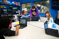 Chance Pendley, Senior Youth Coordinator, helps Dante Lane, 8, inside the robotics room at the Boys and Girls Club of Western Pennsylvania in the Lawrenceville neighborhood on Friday February 19, 2021 in Pittsburgh, Pennsylvania. (Photo by Jared Wickerham/Pittsburgh City Paper)
