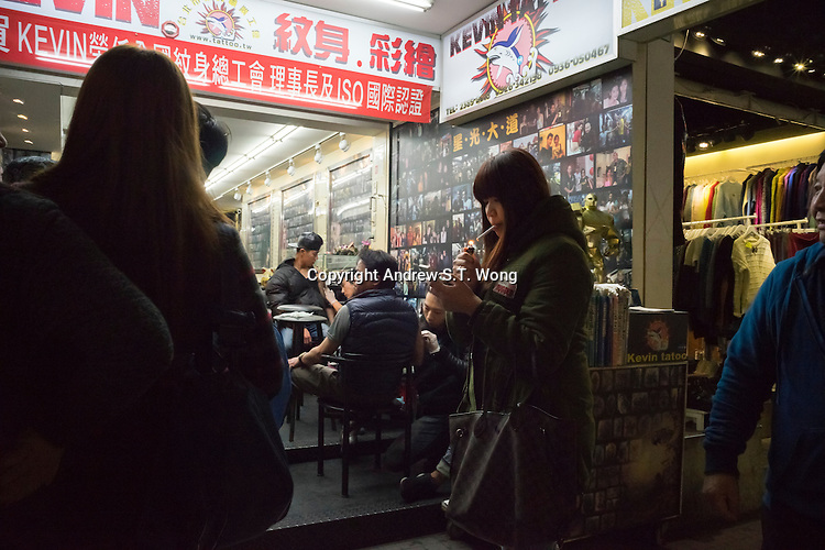 """A young woman lights a cigarette outside a tattoo parlour in Ximending District, Taipei, Taiwan, 2015. Ximending has been a famous area for shopping and entertainment since the 1930s. Historic structures include a concert hall, a historic cinema, and the Red House Theatre. Modern structures house karaoke businesses, art film cinemas, wide-release movie cinemas, electronic stores, and a wide variety of restaurants and fashion clothing stores. The pedestrian area is especially popular with teens and has been called the """"Harajuku"""" of Taipei."""