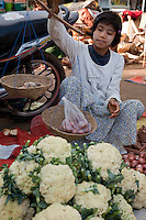 Myanmar, Burma. Young Woman Weighing Onions in a Hand-held Scale.  Bagan Market.