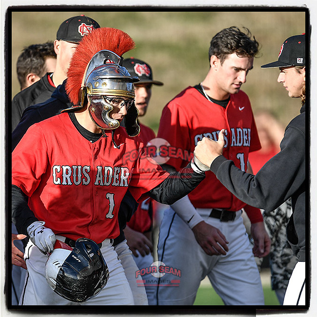 """Left fielder Jared Williams (1) of the North Greenville Crusaders wears the """"Crusader Crusher"""" helmet placed on his head by teammates after he hit a two-run home run in the fifth inning of a game against the Palm Beach Atlantic Sailfish on Monday, February 25, 2019, at Ashmore Park in Tigerville, South Carolina. Palm Beach won, 7-5. (Tom Priddy/Four Seam Images)"""