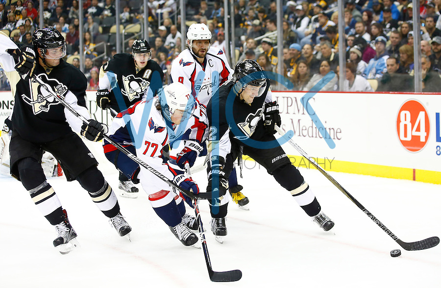 Ben Lovejoy #12 of the Pittsburgh Penguins and T.J. Oshie #77 of the Washington Capitals battle for the puck along the boards in the third period during the game at Consol Energy Center in Pittsburgh, Pennsylvania on December 14, 2015. (Photo by Jared Wickerham / DKPS)