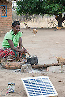 ZAMBIA, Chipata, woman cooks with firewood in village, solar panel for battery recharge / SAMBIA, Chipata, Frau in einem Dorf kocht mit Feuerholz, Solar Panel zur Ladung einer Batterie