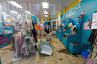 Pictured: A woman clears up items from a flood in Poundland store in Pontypridd, Wales, UK. Sunday 16 February 2020<br /> Re: Storm Dennis has been affecting parts of Wales, UK.