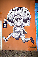Oaxaca, Mexico, North America.  Day of the Dead Celebrations.  Wall Mural of a Dancing Skeleton Holding a Bottle of Mezcal, a local alcoholic liquor made from the heart of the agave (maguey) plant.  This figure is part of a larger mural announcing the date and time of the neighborhood comparsa, a procession for honoring the memory of the dead.