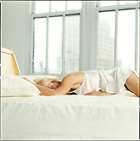 Woman in bed with windows in background<br />