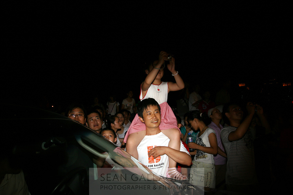 CHINA. Beijing. People in the Olympic village whilst watching rehearsals for the Beijing Olympic games. 2008