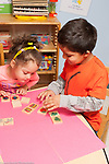 Education preschool 4 year olds boy and girl playing memory game with picture tiles