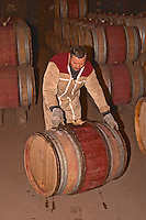 A man in the barrel cellar moving a barrique by rolling it. Domaine M Chapoutier, Tain l'Hermitage, Drome Drôme, France Europe