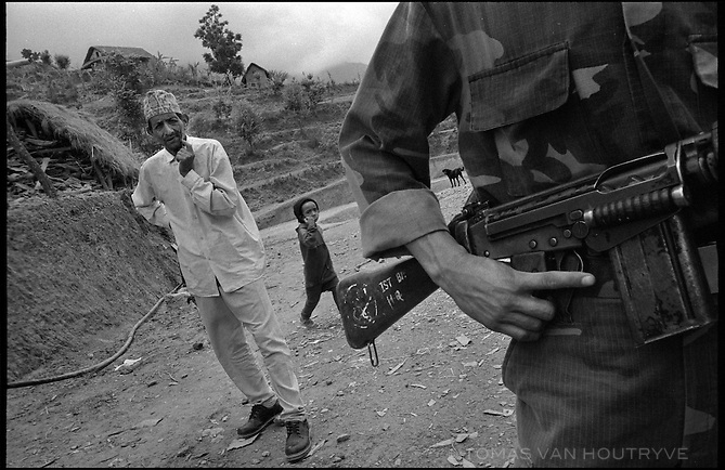 """A Maoist rebel soldier of the People's Liberation Army stands guard before the inauguration ceremony for the Maoist rebel """"Martyr's Road,"""" celebrating the opening of the first section of the road in Tila, Nepal on 24 June, 2005.<br />"""
