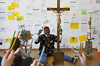 Switzerland. Canton Ticino. Barbengo. Elementary school. Don Gerald Chukwudi Ani is a catholic priest from Nigeria. He teaches religions' history to children. Wearing a boubou printed with lion's heads and a red hat, he sits on the floor. His two legs surround a crucifix one meter in height. He has on his left a paschal candle which will be lit on the occasion of the solemn celebrations of the Easter vigil, to mark the expectation of the resurrection of Christ. On his right, placed on a chair, olive branches recall the triumphal entry of Jesus into Jerusalem under the cheering of the crowd waving palms. The teacher and his pupils hold in their hands colorful pencils and original Stabilo Boss Highlighters. Drawings on the wall. Barbengo is a quarter of the city of Lugano. 23.03.2018 © 2018 Didier Ruef