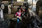 Workers process raw hides on a frizing machine at a tannery in the Bantala area of Kolkata, West Bengal, India.
